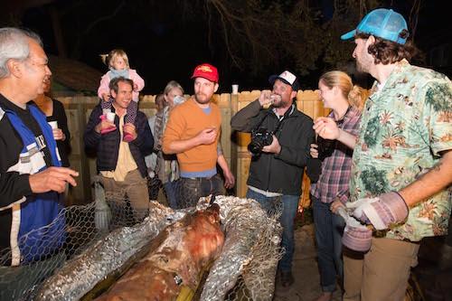 Men enjoying night party with roasted pig.