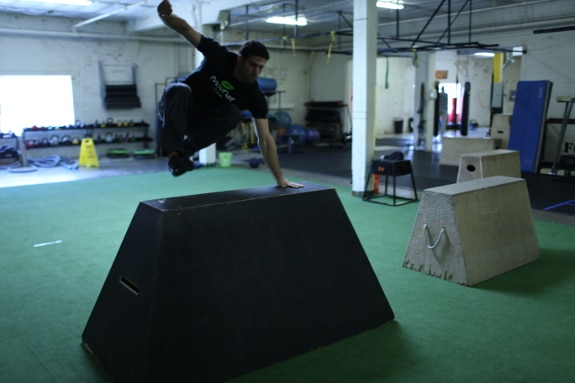 man vaulting jumping over concrete barrier movnat workshop