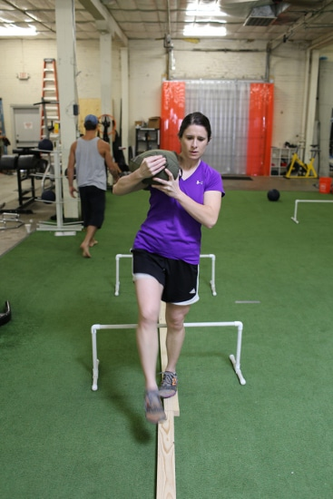 woman carrying sandbag while balancing on 2x4 movnat workshop