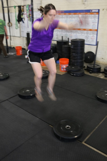 woman jumping from weight plate to weight plate movnat workshop