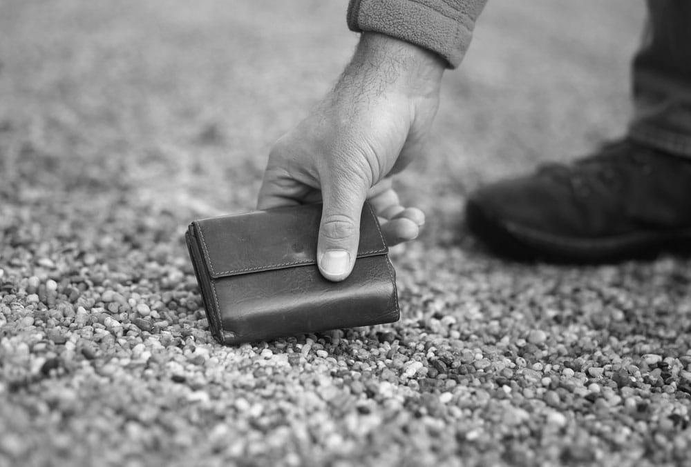 man picking wallet up off ground black white photo