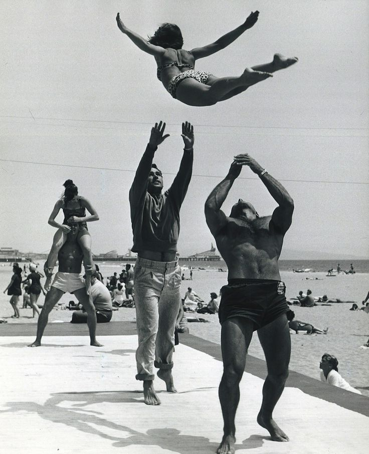 vintage men on beach throwing woman into air