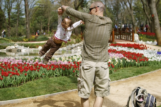 Dad swinging little girl by arms at botanical garden with bag placed on the floor.