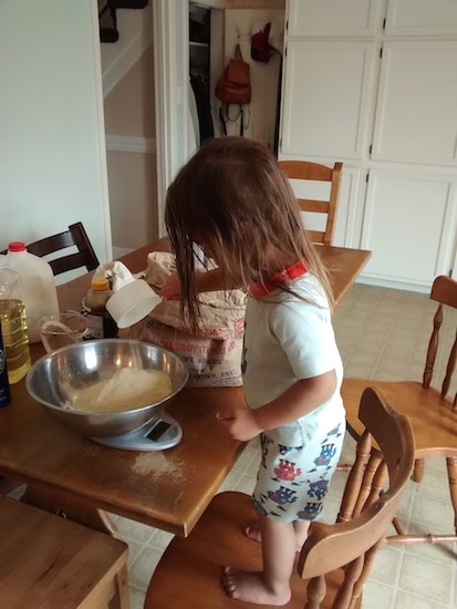 Little girl pouring flour into mixing bowl making bread while standing on a chair.