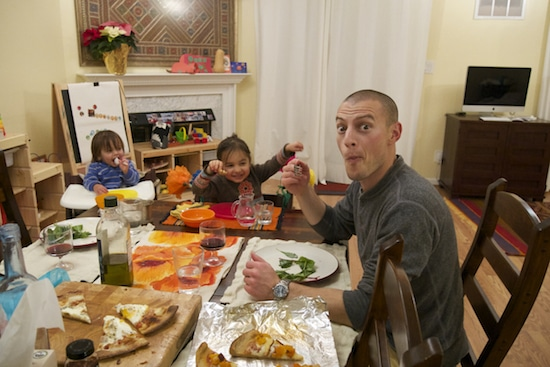Dad making funny face while eating dinner with kids.