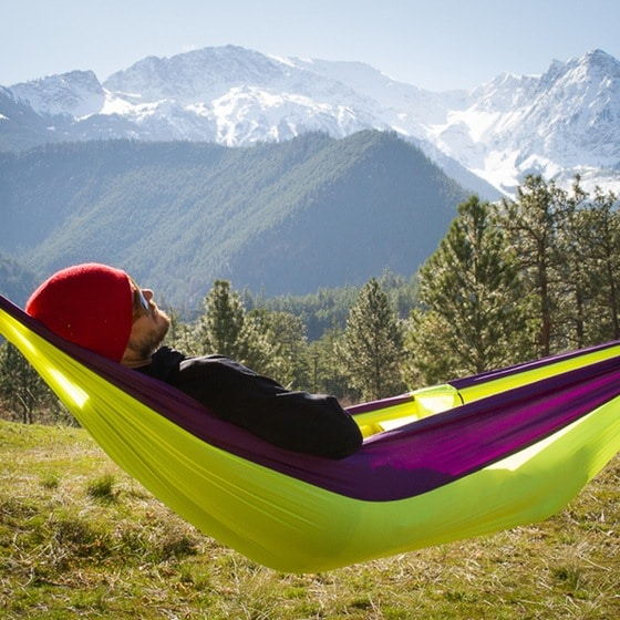 Man napping relaxing on hammock with mountains in background.