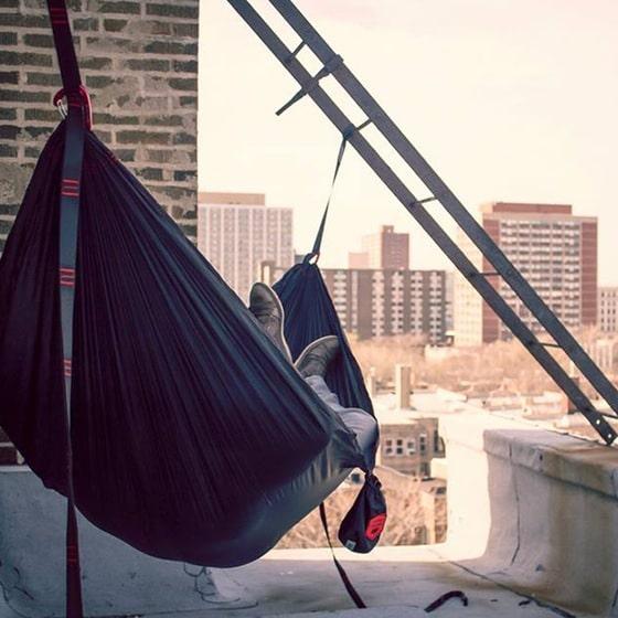 Man sleeping in hammock on city rooftop.