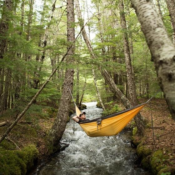 Hammock camping man relaxing in hammock over river.