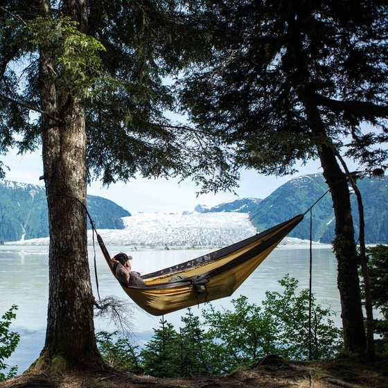 Man relaxing napping in hammock with glacier in background.