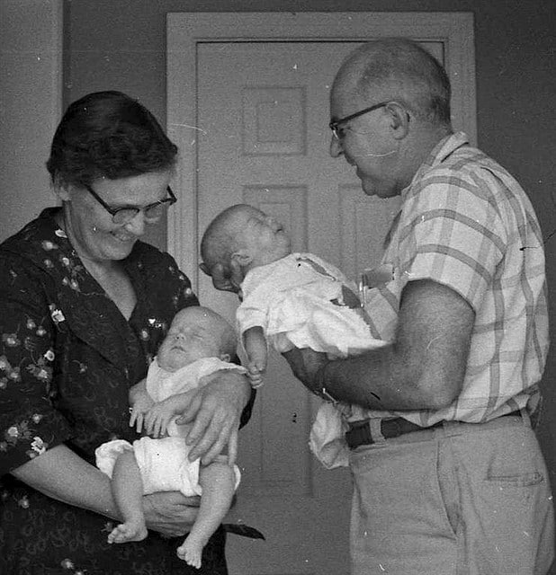 vintage grandparents holding baby grandchildren