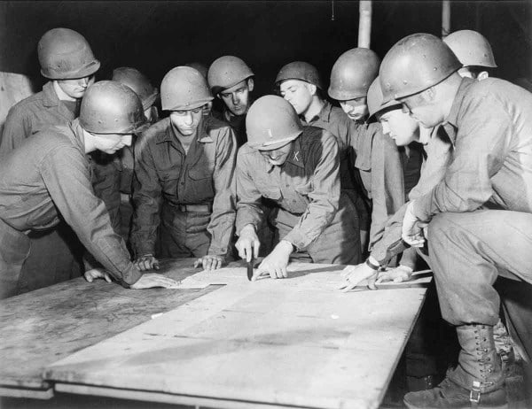 vintage soldiers looking at map on table