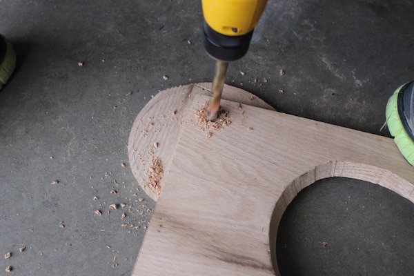 Drilling a hole at the corner of wooden board.