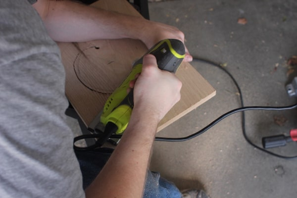 A man using a jig saw for cutting plant tray circle.
