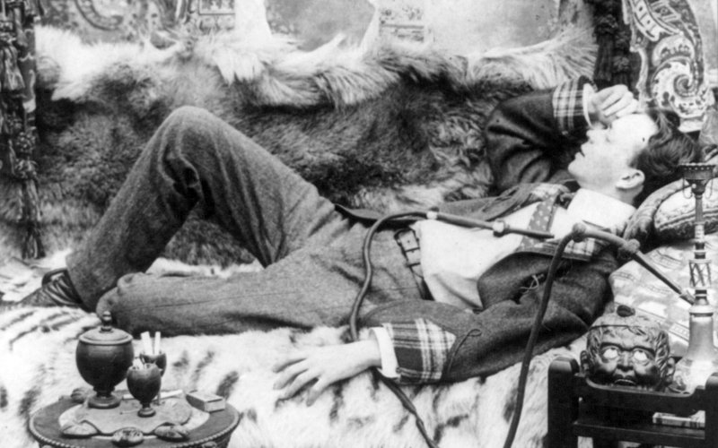 vintage young man lying on couch napping with furs