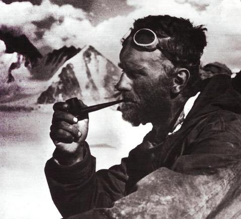 vintage explorer with aviation goggle smoking pipe in mountains