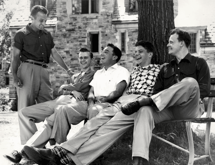 vintage young friends sitting on bench laughing talking