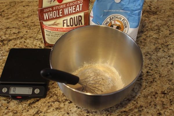 Measuring flour batter in a steel bowl.