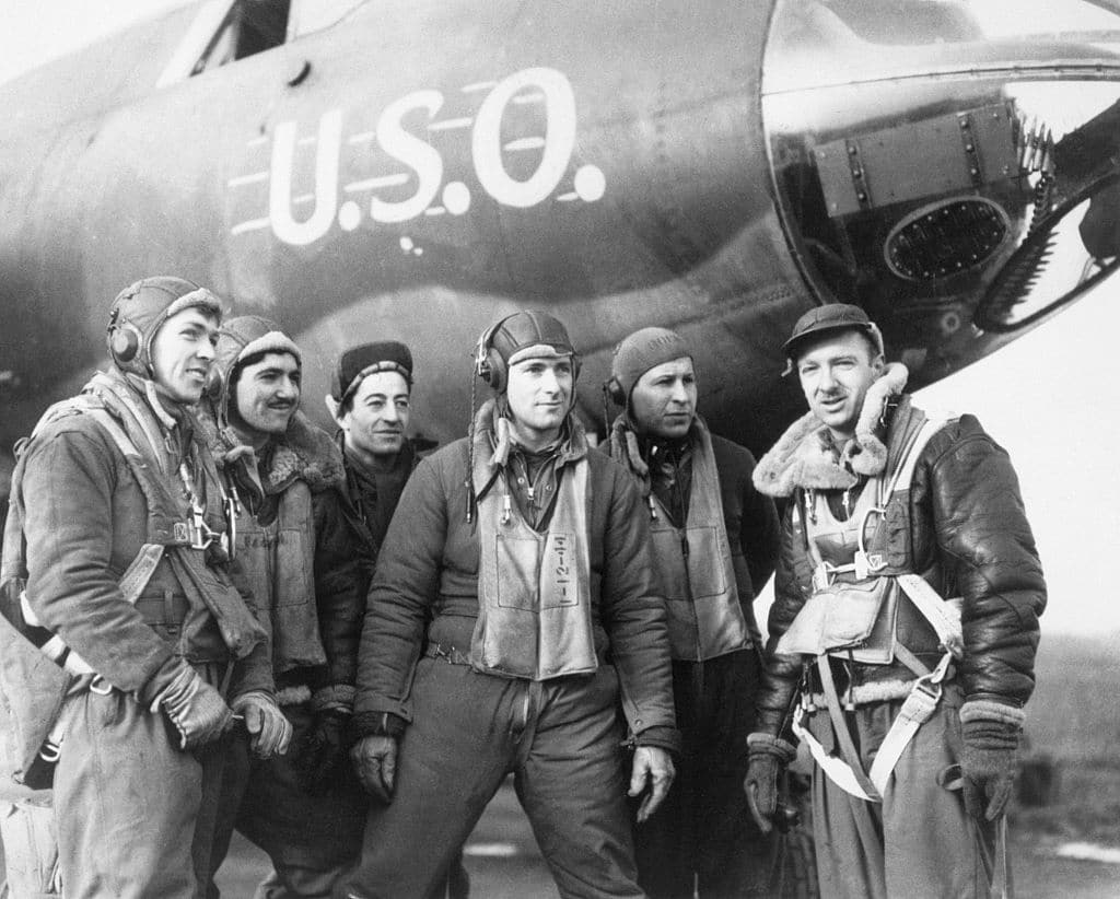 Walter cronkite with soldiers in front of airplane.
