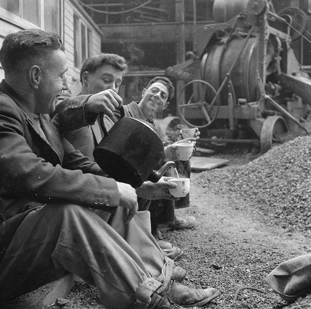 vintage laborers pouring tea from a kettle on a break