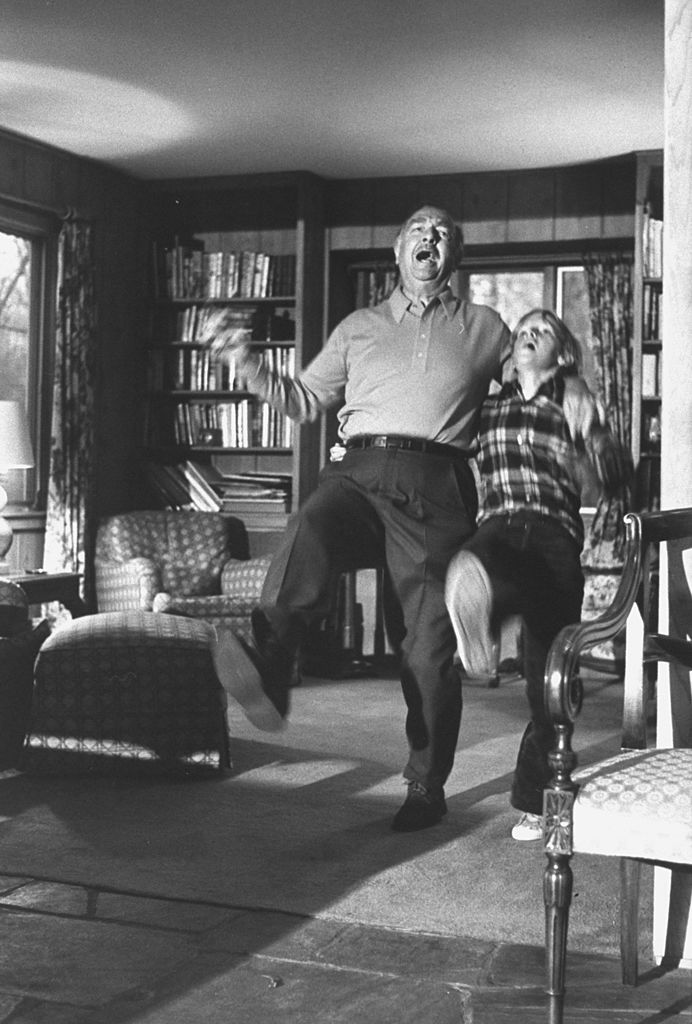 Walter cronkite dancing laughing with son in living room.