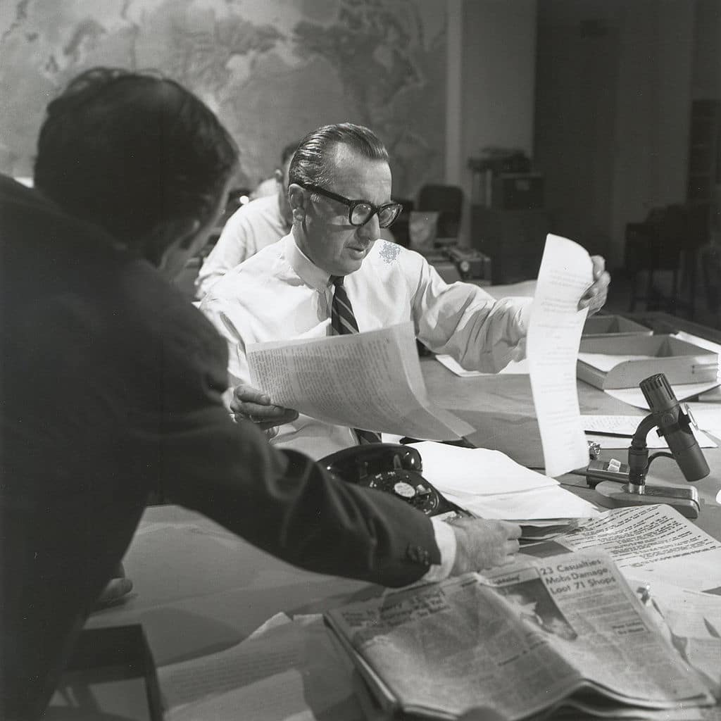 Walter cronkite working sorting through papers at news desk.