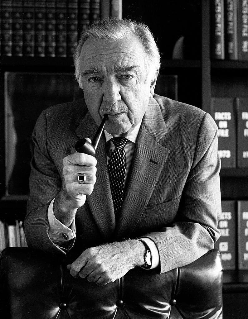 Older walter cronkite with tobacco pipe.