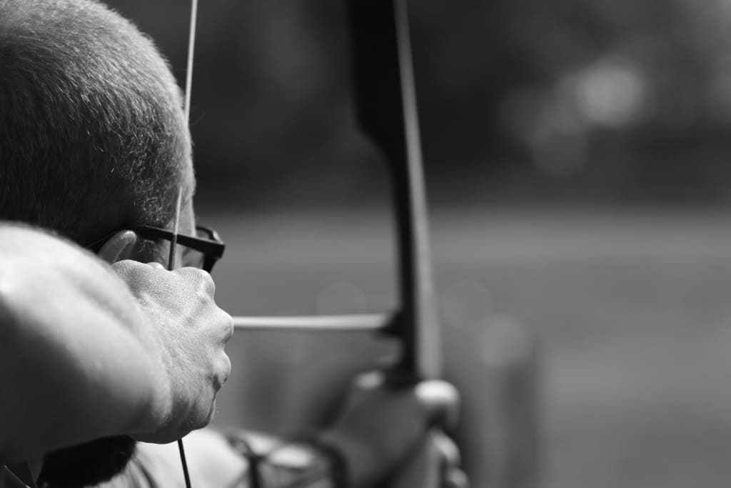 man shooting bow and arrow black white close up