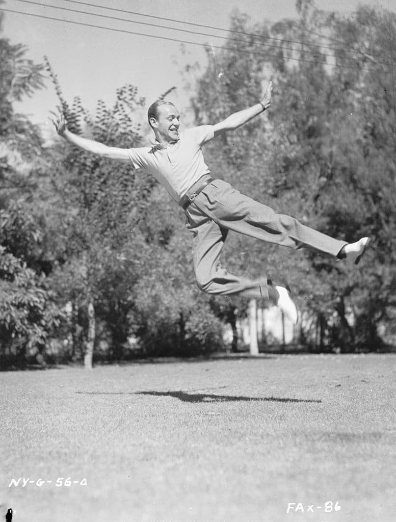 vintage man jumping in the air wearing pleated pants