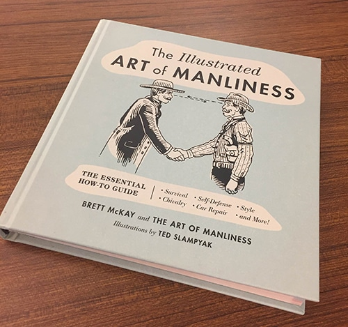 Illustrated art of manliness hardcover book on table.