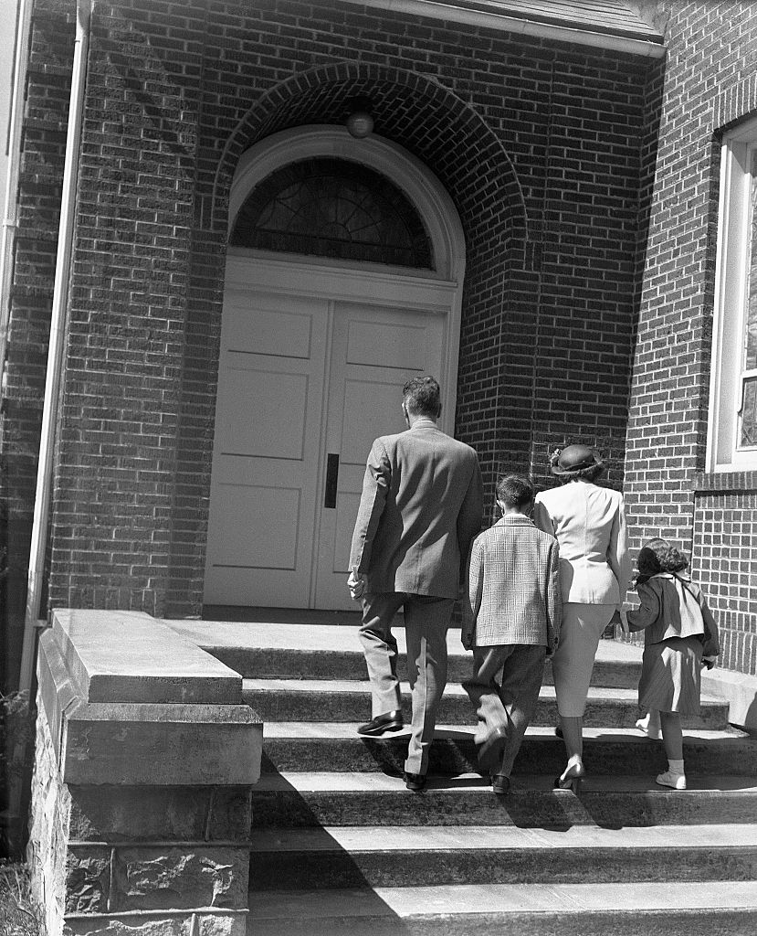 vintage family walking up stairs to church