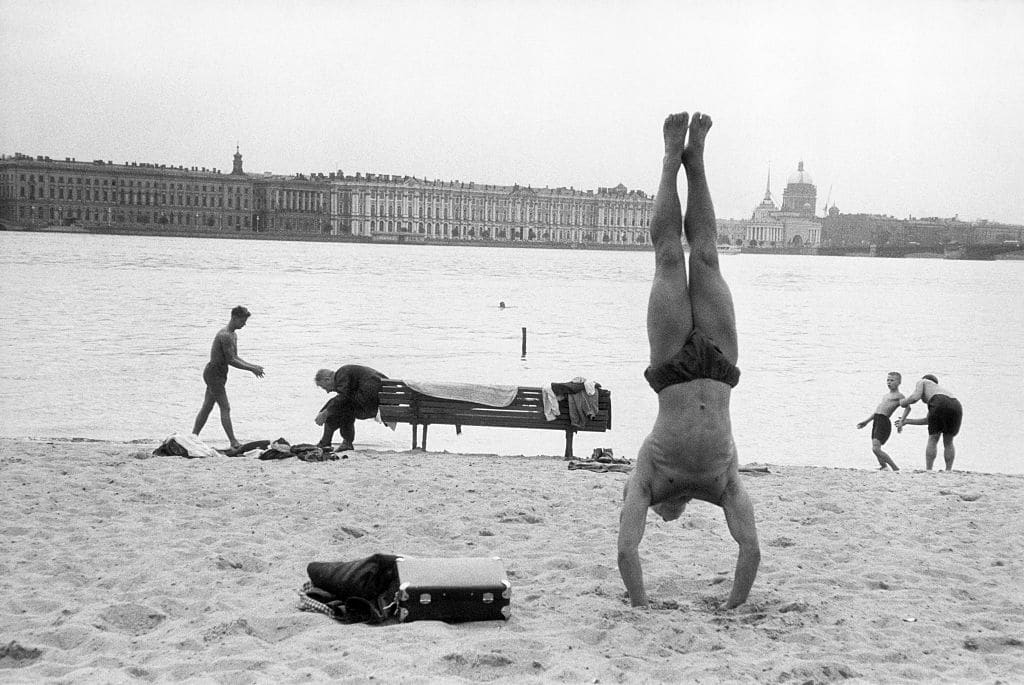 vintage man doing handstand on beach