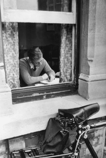 Man sitting at window writing something on paper.