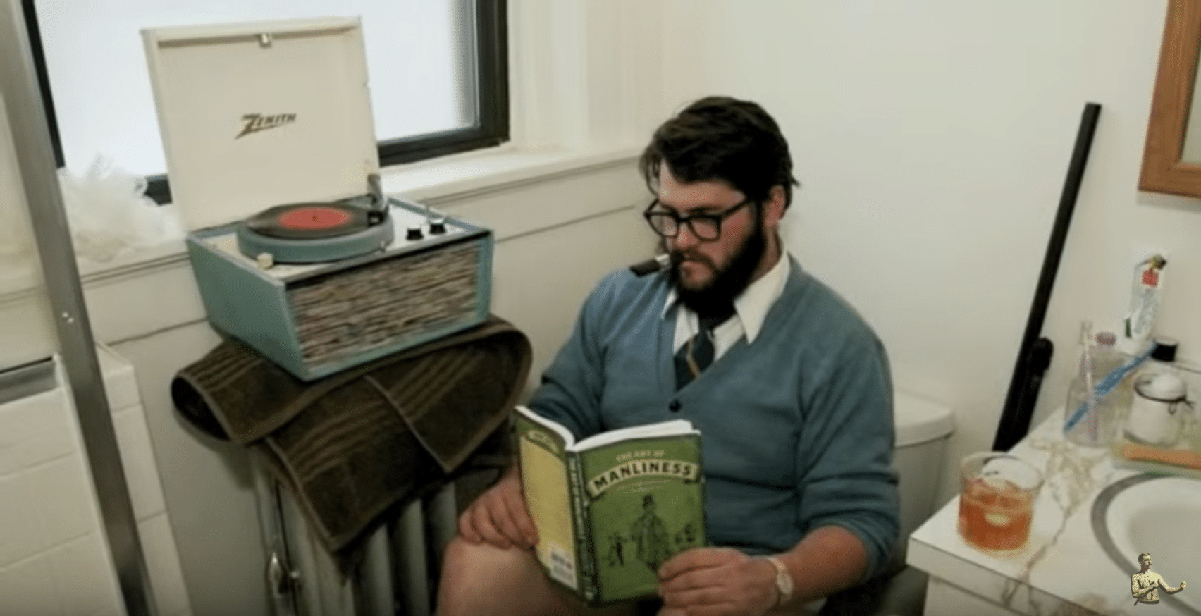 A man reading a book in a toilet.