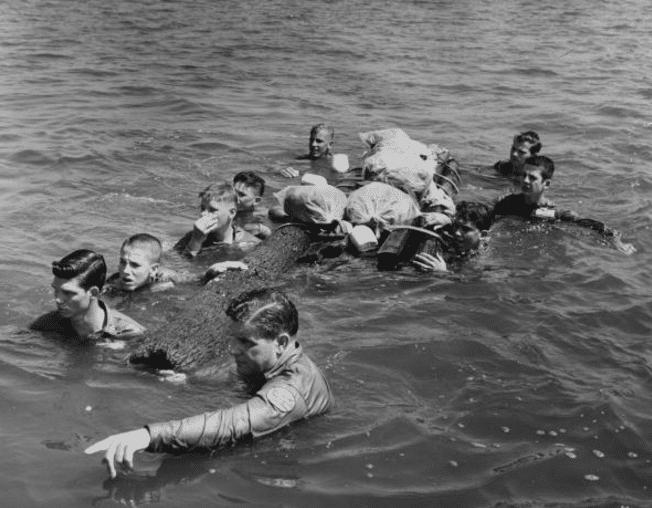 vintage men swimming across river training exercise