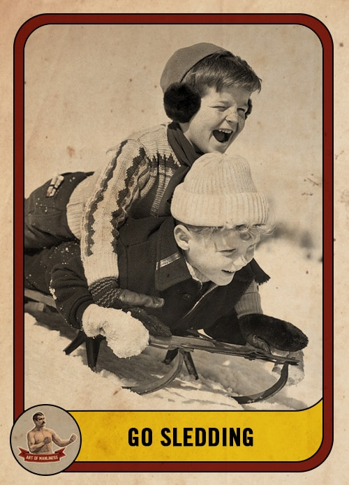 vintage boys sledding down a hill on a toboggan