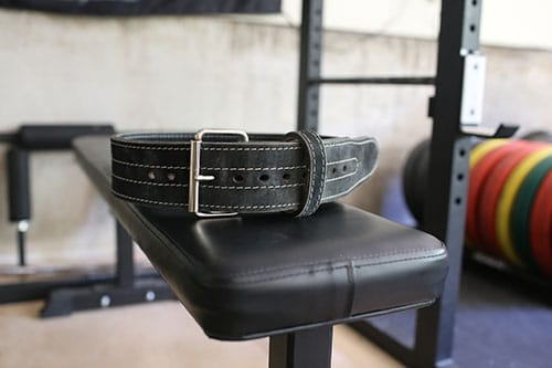 Black leather weightlifting belt on a bench.