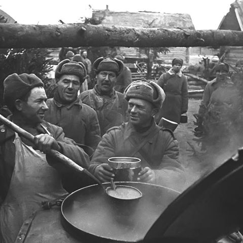 Vintage soldiers standing around big pot of soup for their turn.