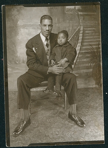 vintage man holding son in lap for portrait
