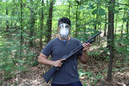 Man with improvised gas mask and shotgun zombie survival in a forest.