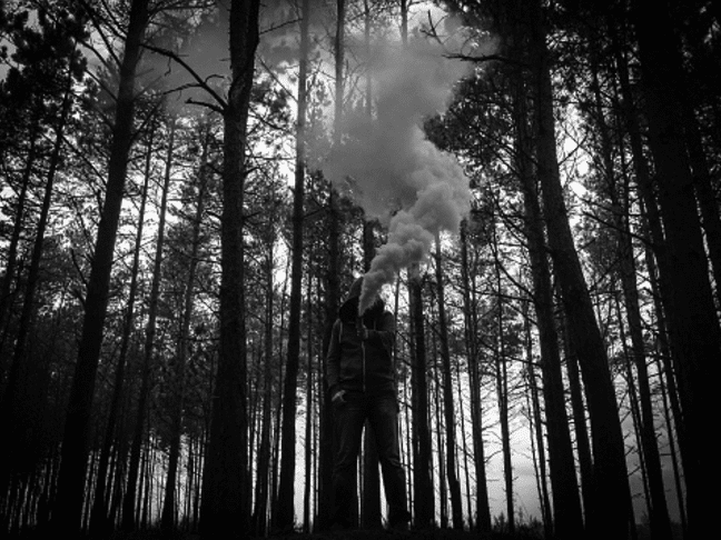 man in woods with smoke bomb black white