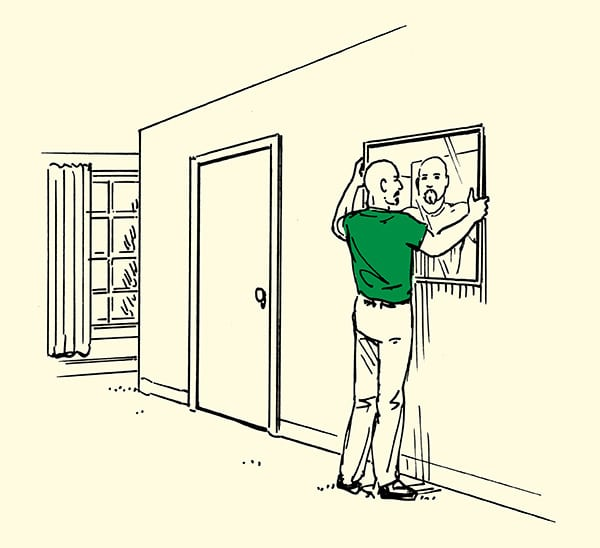 Man placing mirror on wall in home illustration.