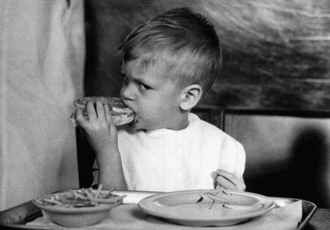Vintage small boy eating a sandwich looks angry.