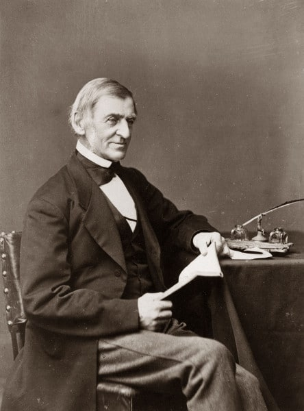 ralph waldo emerson at a table with a book