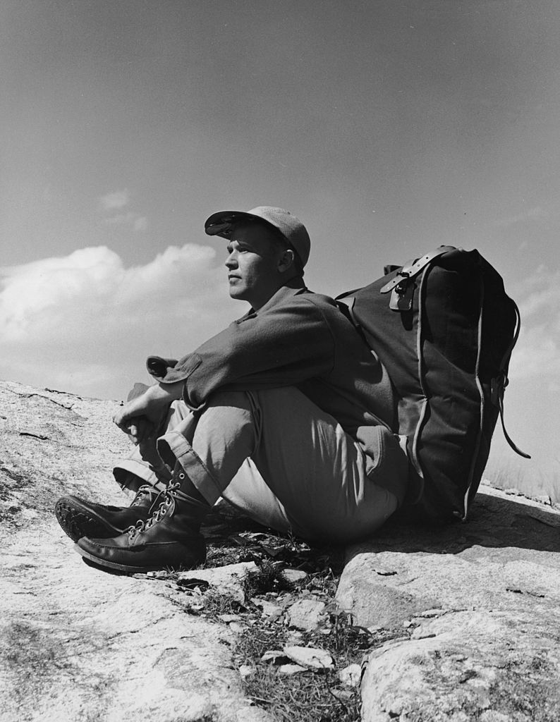 Vintage man hiking sitting on a mountain with a backpack.