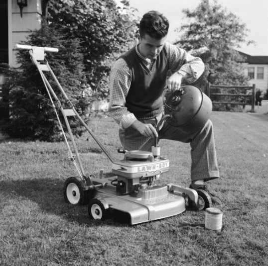 vintage man pouring gasoline into lawn mower