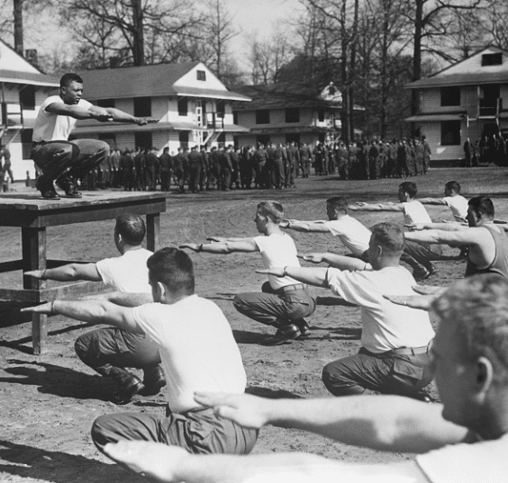 Vintage army pt training men squatting.