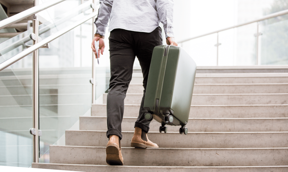 A man stepping up the stairs with traveling hand bag.