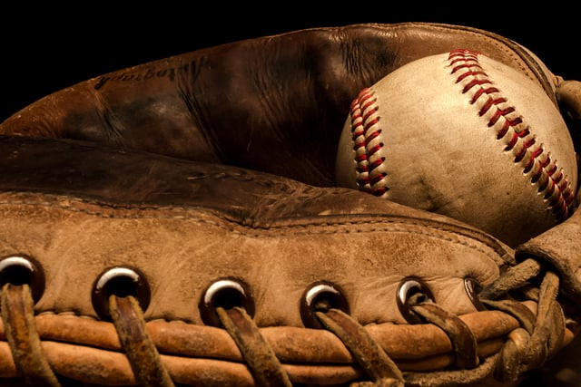 vintage worn leather baseball glove with a ball