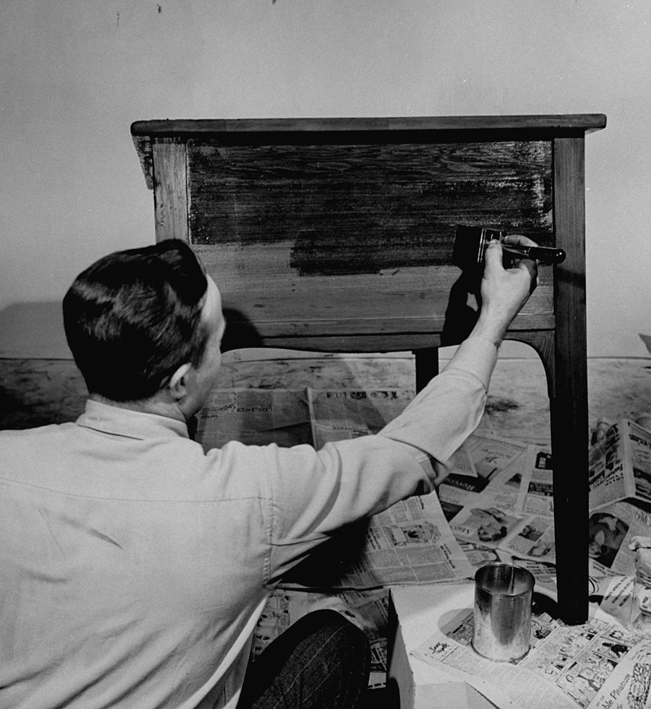 vintage man applying wood finish to side table