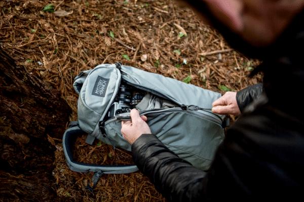 A man unzipping a Hand carry cloth bag.